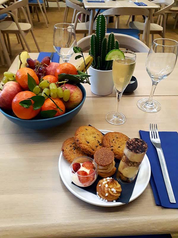 table de restaurant avec un cactus, une coupe de fruits frais, de cookies, biscuits, tiramisu, chouquette, paris brest, coupe de vin pétillant pour le meilleur brunch de nantes